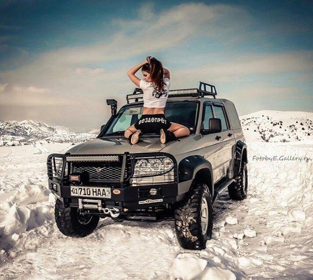Красивая девушка грееся на капоте УАЗ